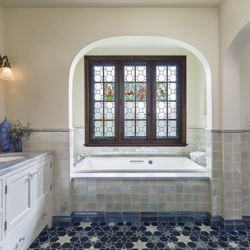 Master bathroom with beautiful aqua and blue tile and stained glass window in bathtub nook