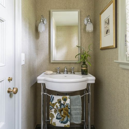 Small powder room with washstand and grasscloth wallpaper